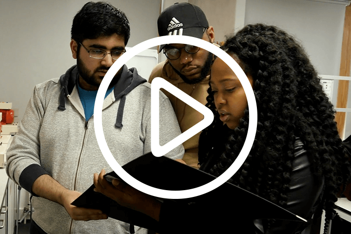 three students in conversation, with play button icon