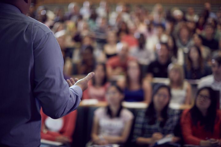 academic delivering presentation in lecture theatre