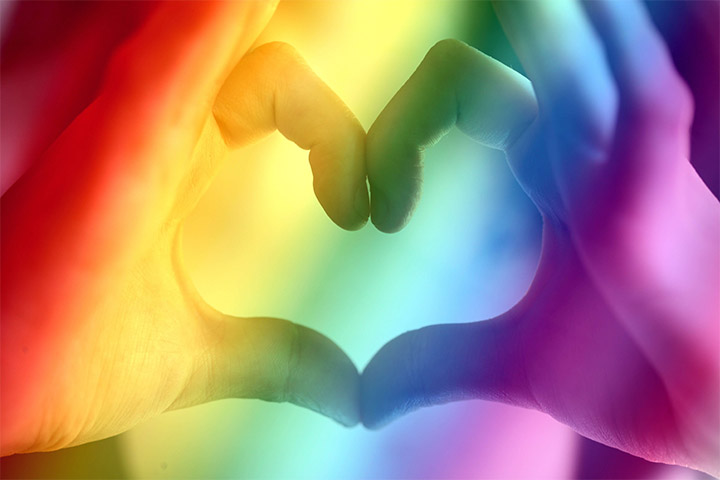 Fingers in the shape of a heart with a rainbow overlay