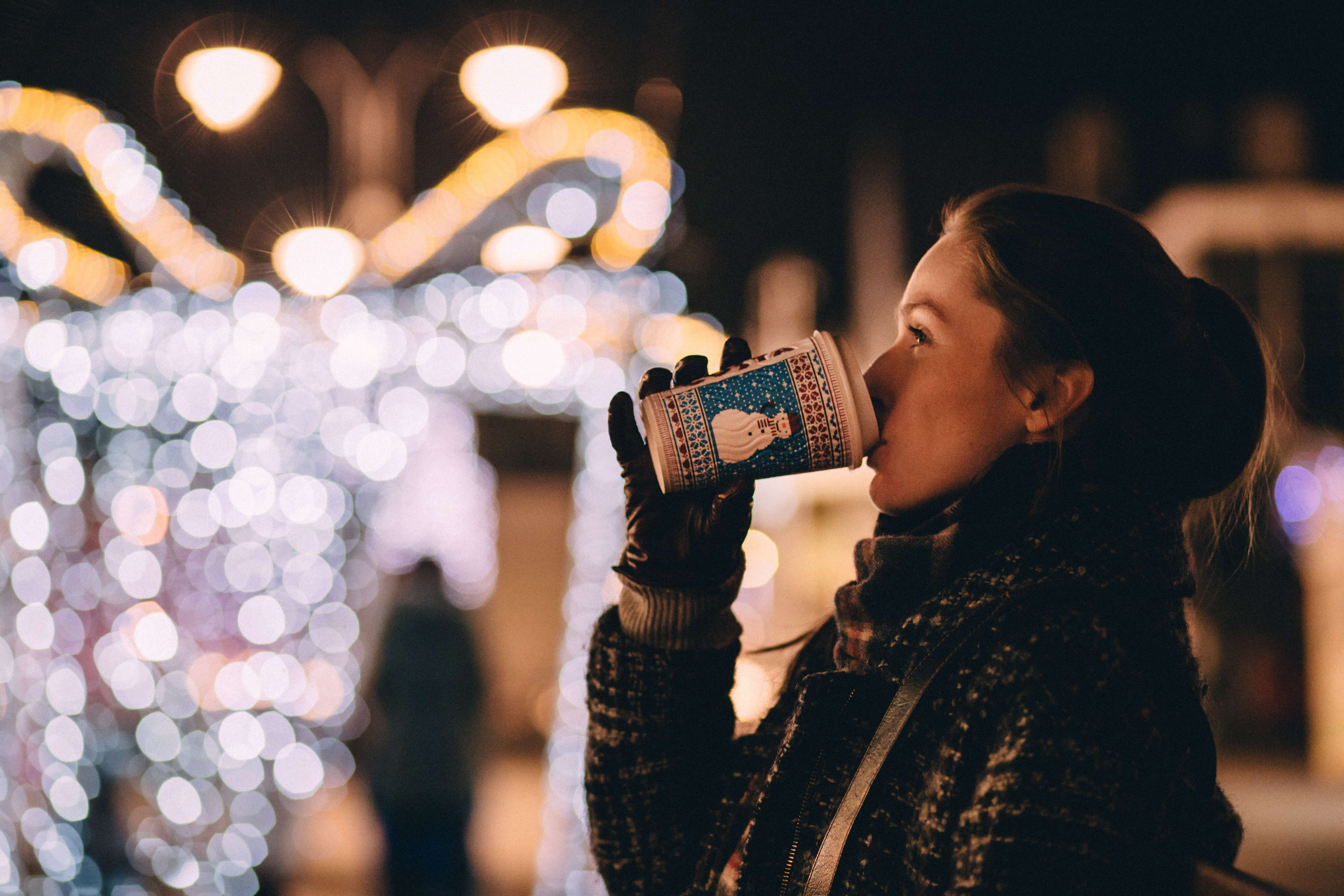 Student outside with hot drink at christmas