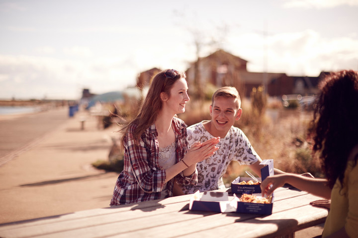 Students enjoying fish and chips at the beach