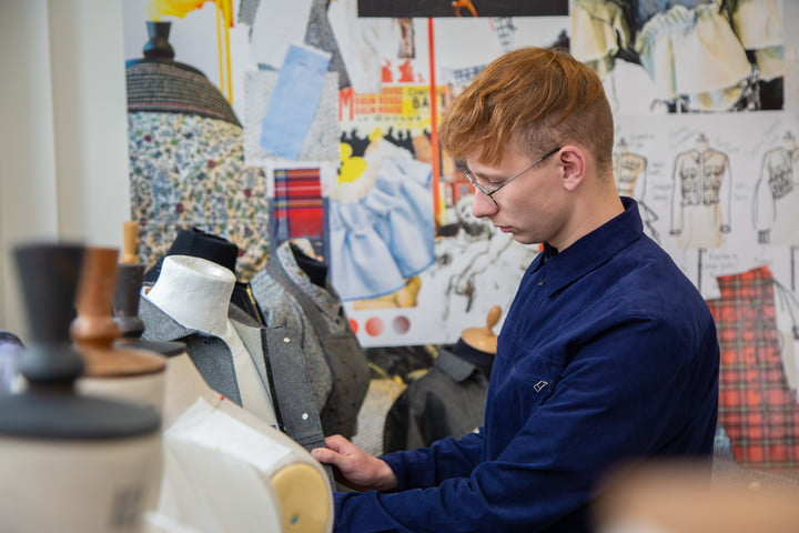 A student adjusting a garment on a mannequin, surrounded by other garments and designs, in a fashion studio