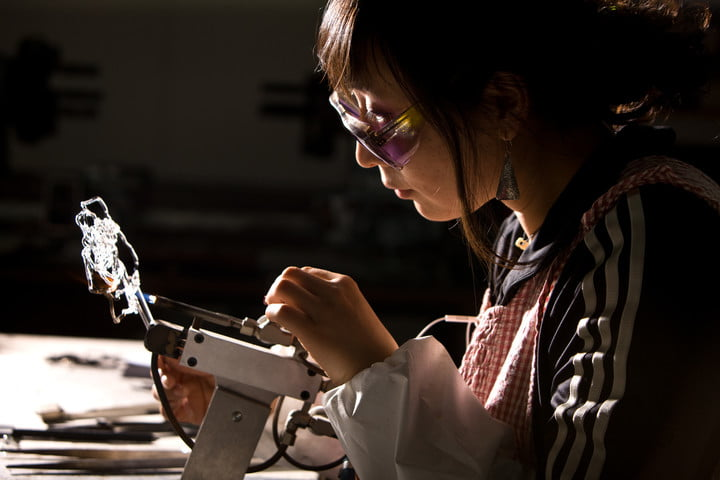 A student wearing safety goggles, working on some glass lampwork in a studio