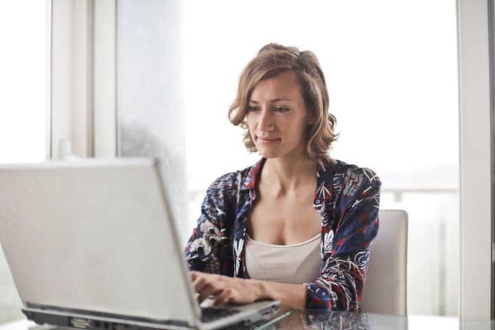 Woman in floral top using a laptop, working from home