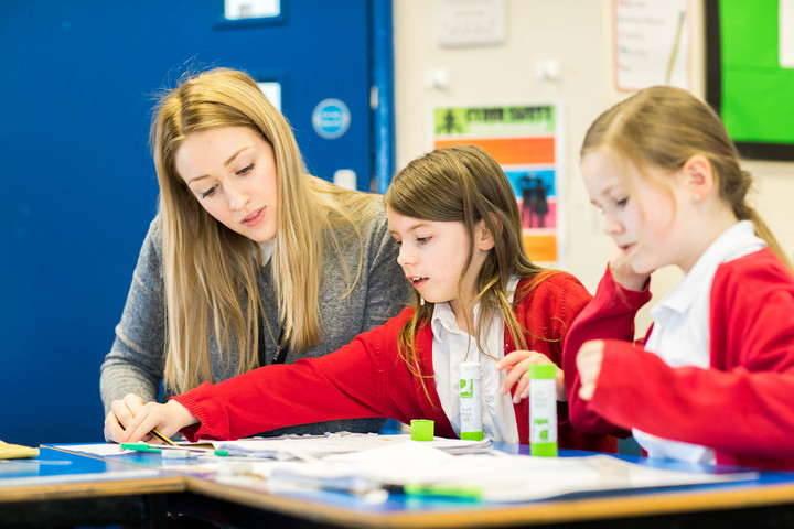 A female teacher is sitting in a classroom, helping two primary school children with their work
