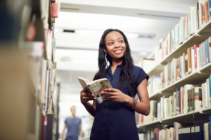 A female student is standing in the library holding a book and smiling to something off camera
