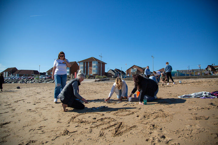 A group of people playing in the sand on a beach