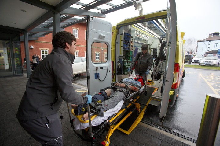 Two student paramedics are moving a patient on a trolley onto the training ambulance