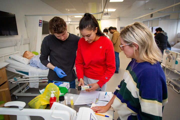 A group of pharmacy students are practicing clinical skills in the mock hospital ward