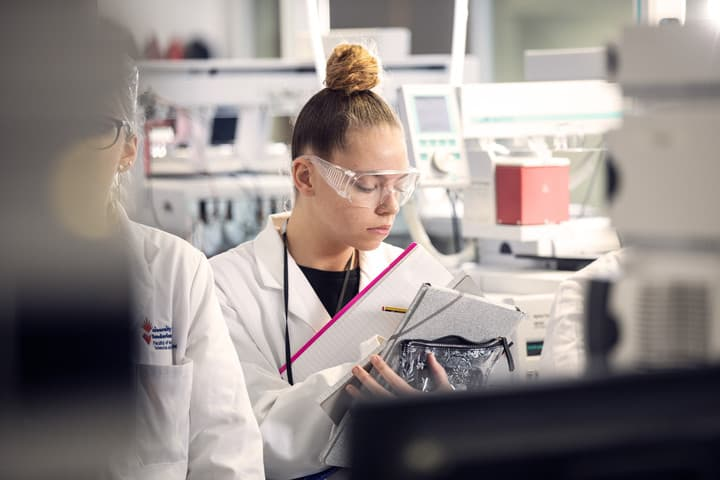 Female student writing a report in analytical lab