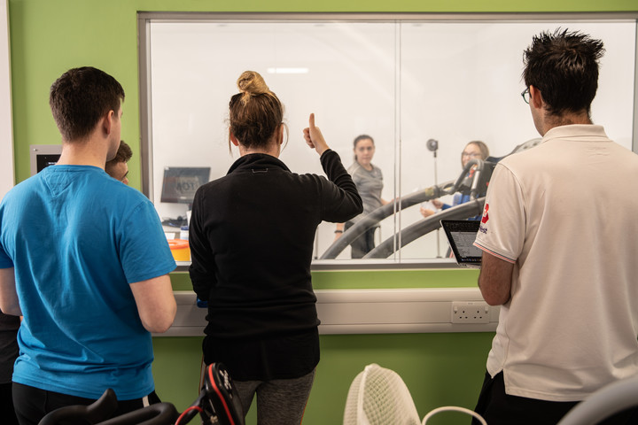 A group of sports students are standing outside the environmental chamber watching two students in the chamber undertake a reaction test