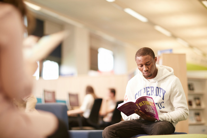 A male student reading a book