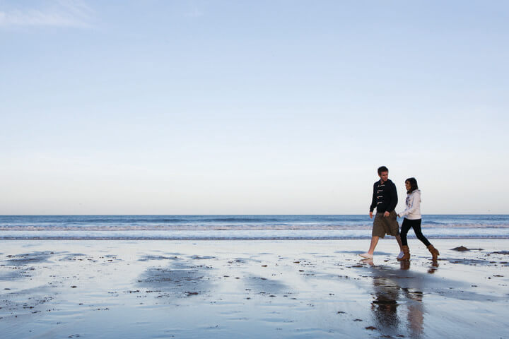 2 students walking along the beach