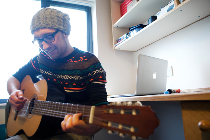 A male student playing the guitar in University-managed accommodation