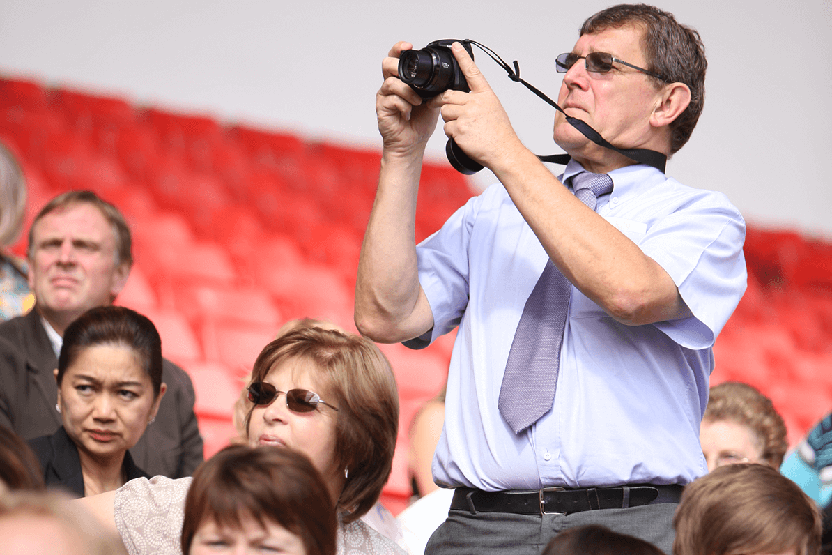 Father taking picture at graduation
