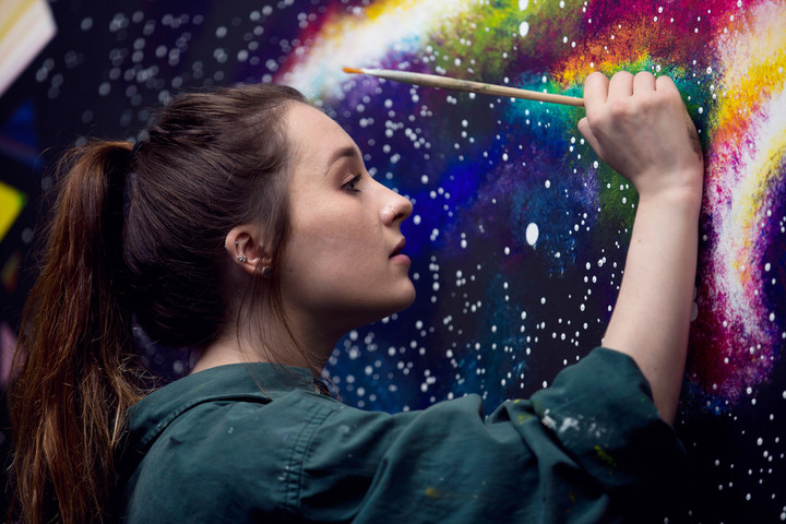 A female student is painting a colourful mural onto a studio wall