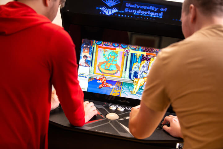 2 computing students playing on an arcade cabinet