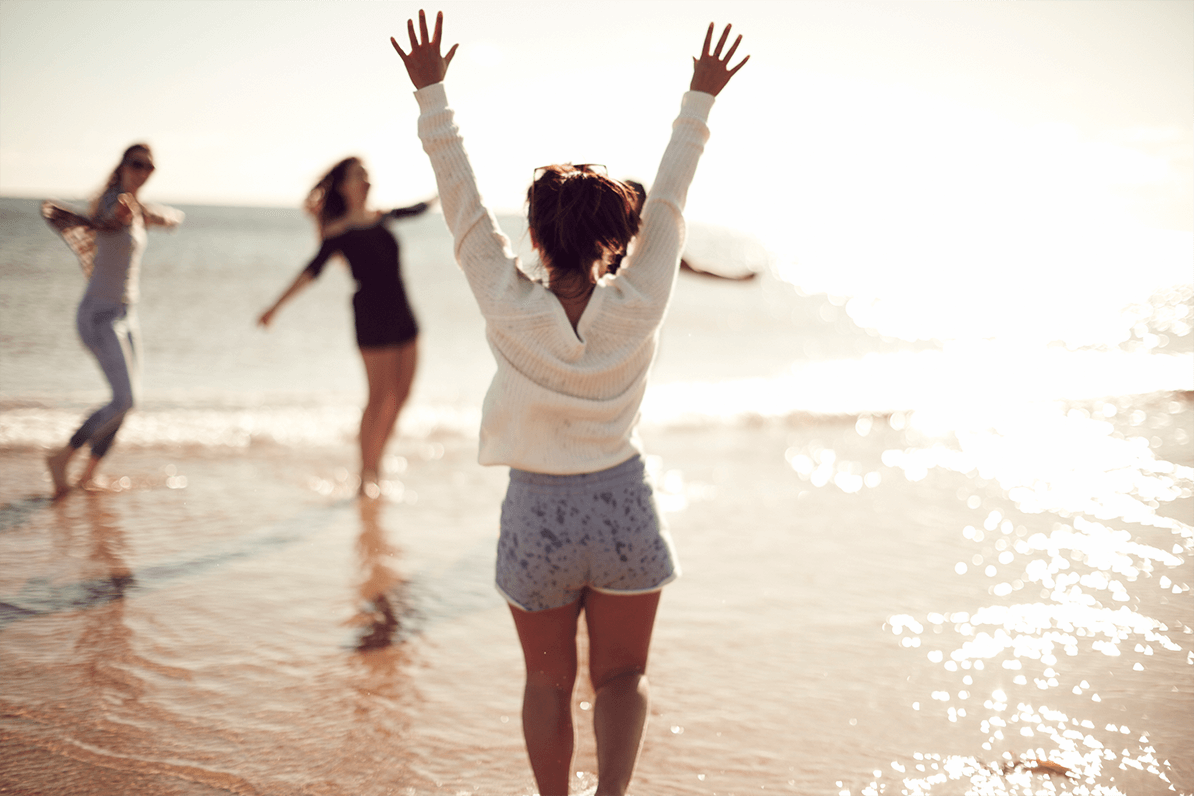 student jumping on beach