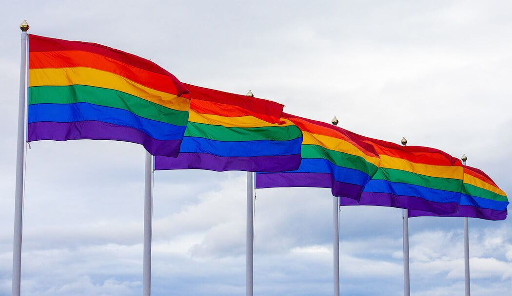 An image of a rainbow flag blowing in the wind