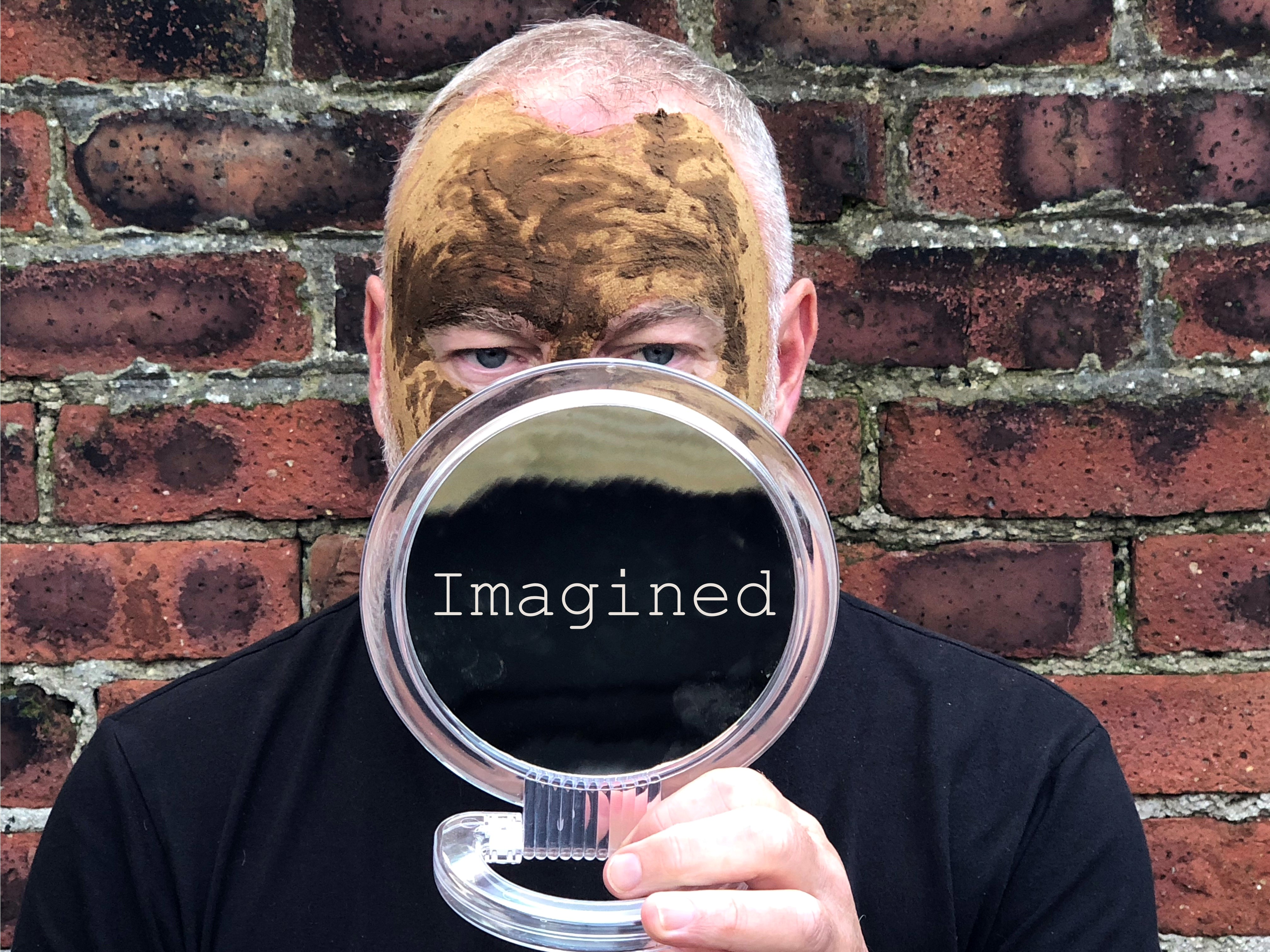 A man against a brick wall looking from behind a round mirror