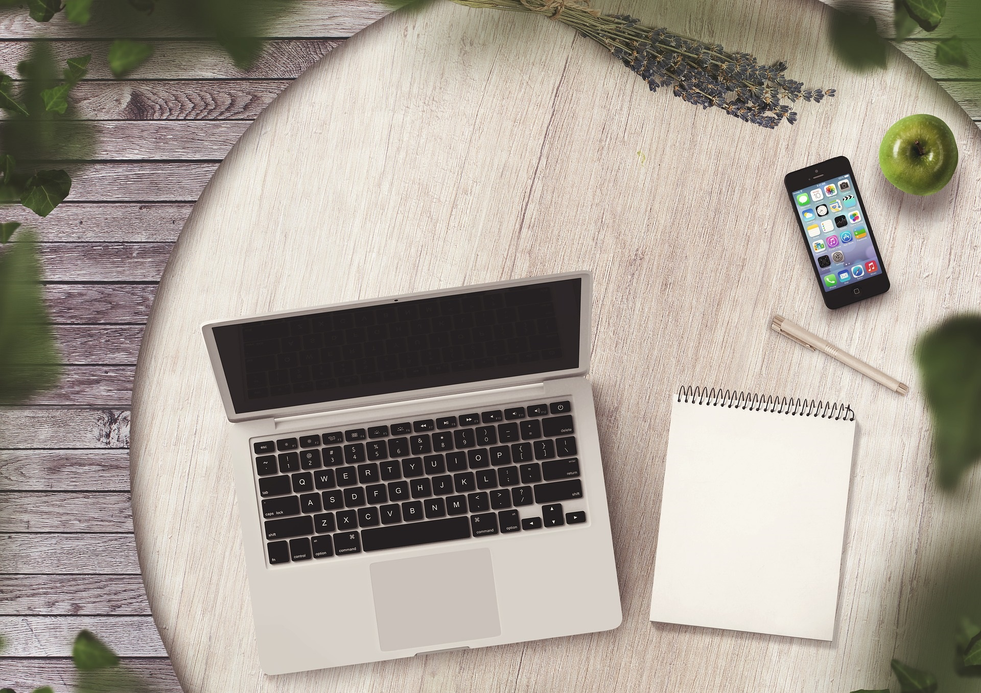 Laptop, note pad and mobile phone on a table
