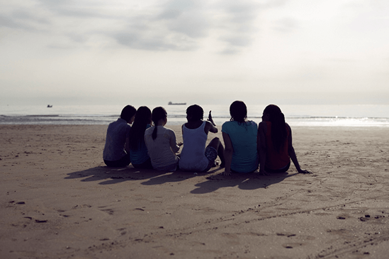 students sitting on beach