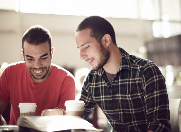 Two students smiling and reading a book