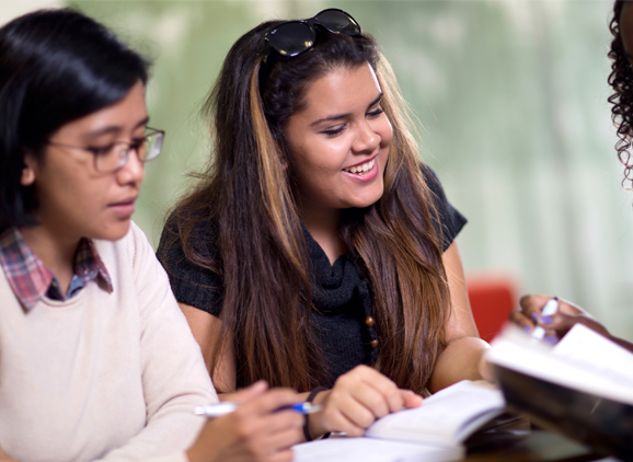 Two students writing in books