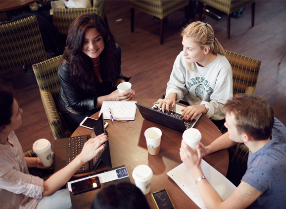 Group of students sat around a table with laptops and coffee