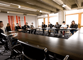 Group of people sat around a boardroom table