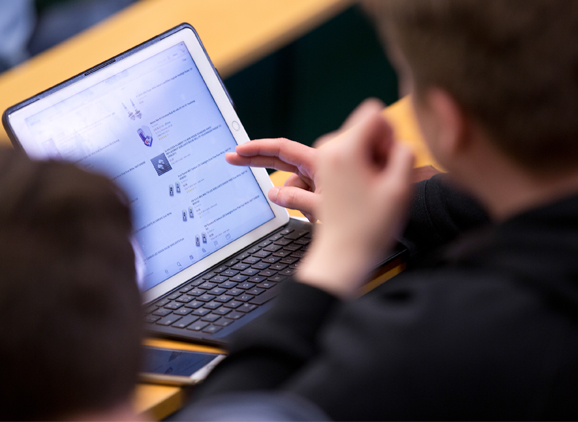 Student using a tablet in lecture theatre