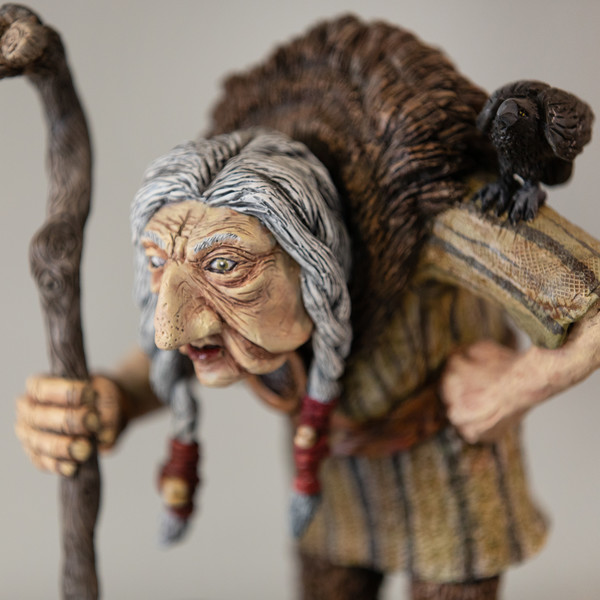 A close up of an animation figurine which is in the shape of an elderly person holding a walking stick