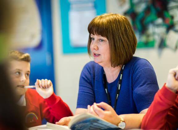 School teacher and pupil talking
