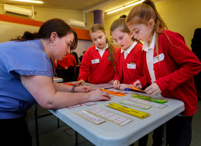 A teacher assisting 3 primary school aged girls with a maths task