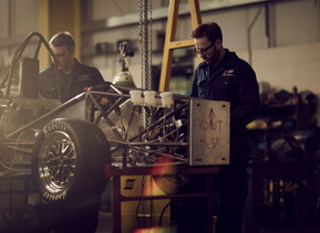 Two students are working on the chassis of the Formula Student car