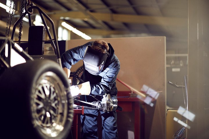 Student welding on a formula student car, wearing a welding mask