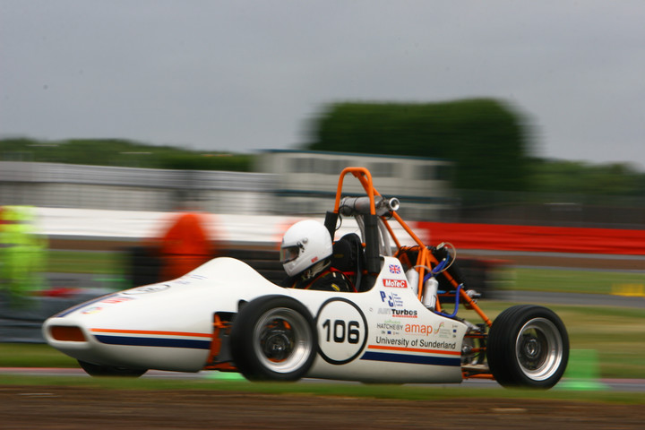The Formula Student car in action, being driven around a race track by a member of the team. The background is blurry to show the speed and motion of the car