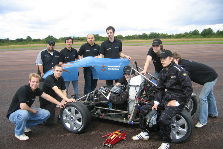 Formula student team standing around the car they have built on a race track, smiling to someone off camera