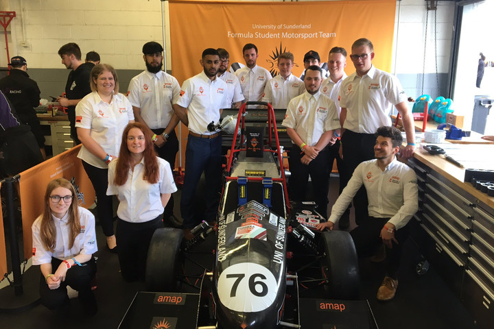 Formula student team standing the car they have built, smiling to camera