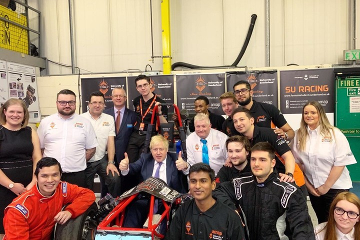 Formula Student Team with Boris Johnson, who is sitting in the Formula Student car