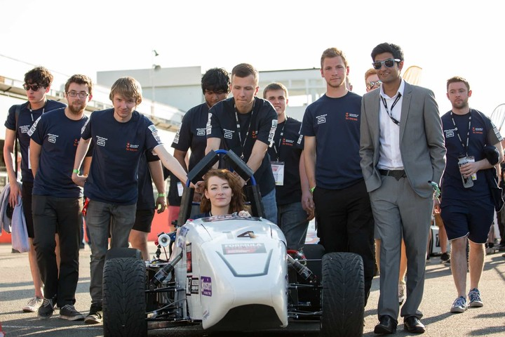 A group photo of the Formula Student team who are standing next to the Formula Student car