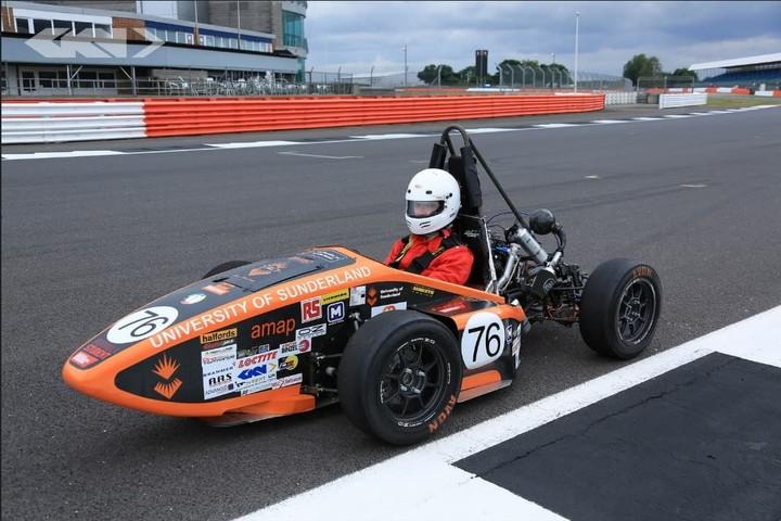 A student is sitting in the Formula Student car on a race track