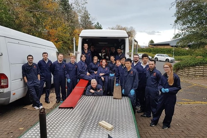 A group photo of the Formula Student team who are standing next to a van