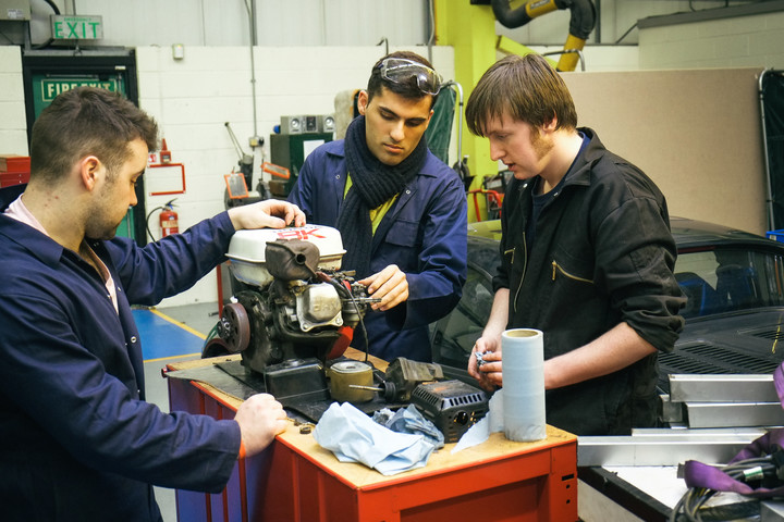 Three male students working on a car engine in the industry centre