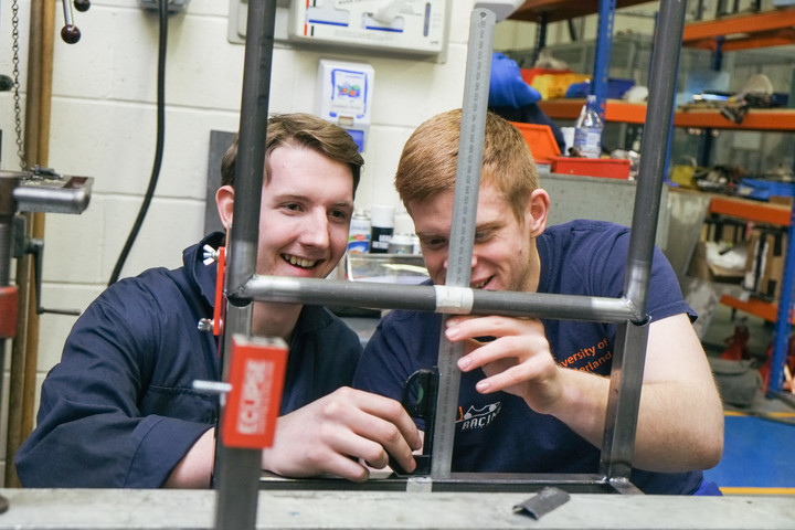 Two male students working on a chassis
