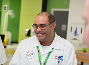 A close up of a male nursing student who is standing in the mock hospital ward and smiling at something off camera