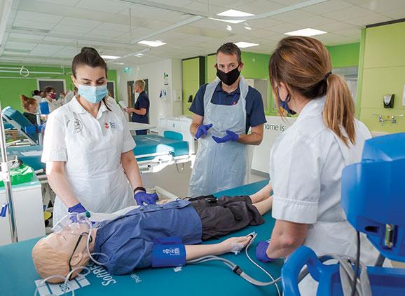 Nursing students in ward attending to manikin