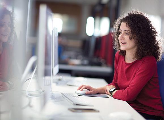 Student sat at a desk looking at computer screen