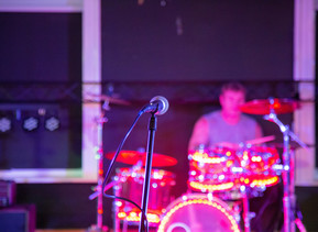 A microphone in the foreground with a person playing drums in the background