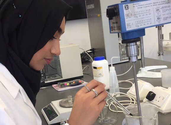 A cosmetic science student working in the lab